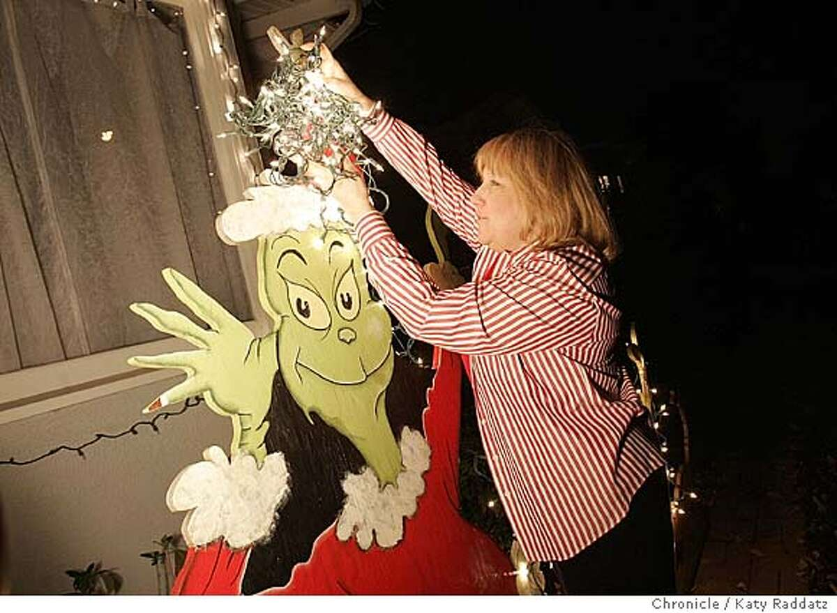 HOLIDAYLANE01_rad.jpg SHOWN: Jeri Morgado (cq) plays untangle-the-Christmas-lights with The Grinch in front of her house on Thompson Ave. in Alameda. Jeri Morgado (cq) is the lady in charge of the committee for Christmas Tree Lane this year, which is Thompson Ave. in Alameda, the street where Jeri and her family live. Katy Raddatz / The Chronicle Ran on: 11-28-2004
