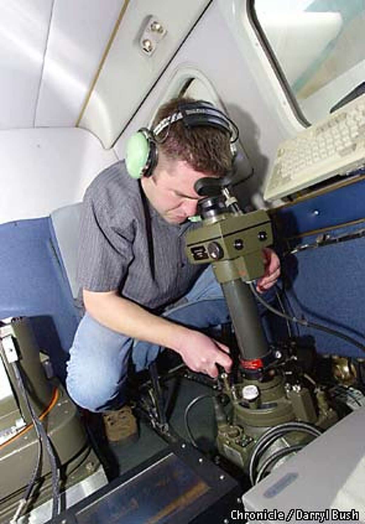 METHODB-C-16FEB03-MT-DB Aerial photographer Erik Sanders of Air Flight Service Co., adjusts camera positioning through a scope which looks down (giving him the camera's line of sight), on the Leica RC-30 aerial mapping camera during flight to photograph the peace march occuring in San Francisco. Chronicle Photo by Darryl Bush