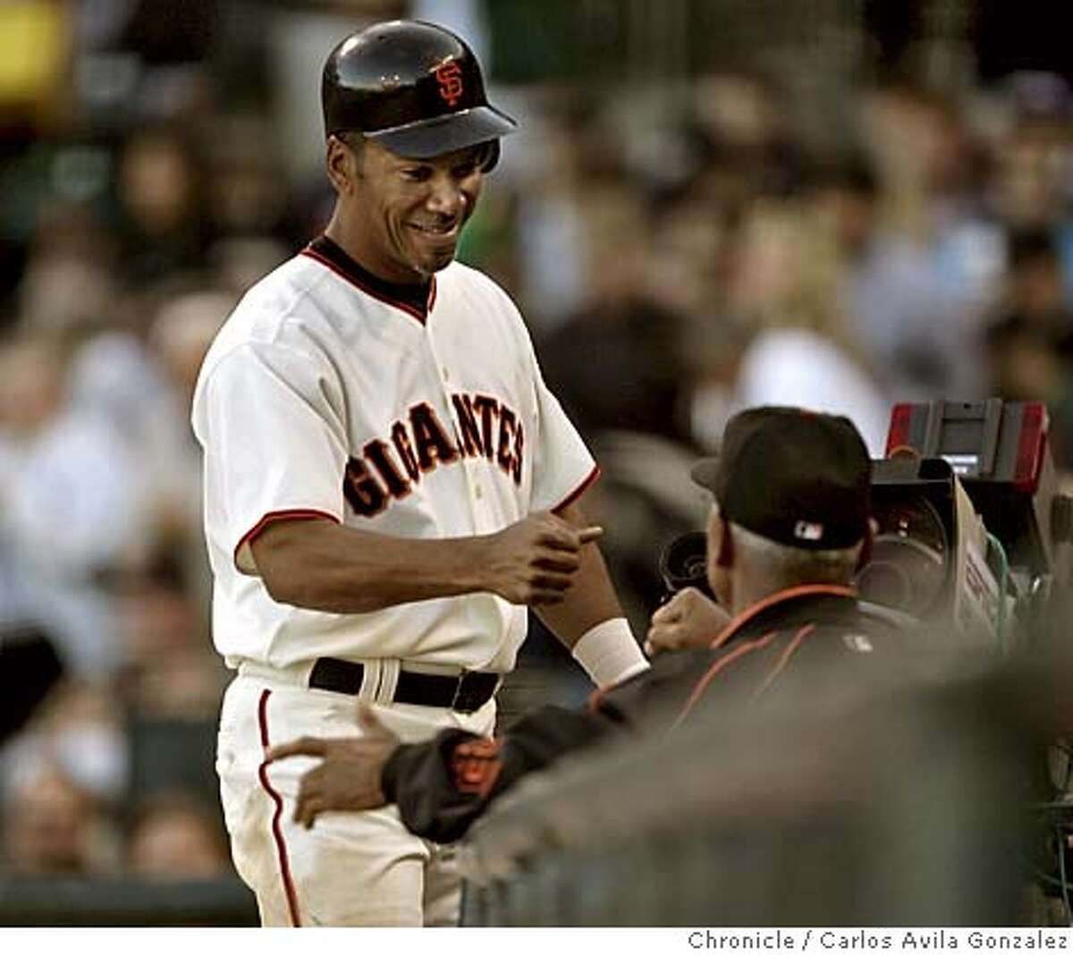 Gigantes' right fielder, Moises Alou, smiles as he is high-fived by his pap�, manager, Felipe Alou after Moises hit a two-run homerun in the bottom of the sixth inning. The San Francisco Giants played the Oakland Athletics at SBC Park in San Francisco, Ca., on Sunday, May 22, 2005. The Giants defeated the Athletics 3-1. Photo by Carlos Avila Gonzalez / The San Francisco Chronicle Photo taken on 5/22/05, in San Francisco,CA.
