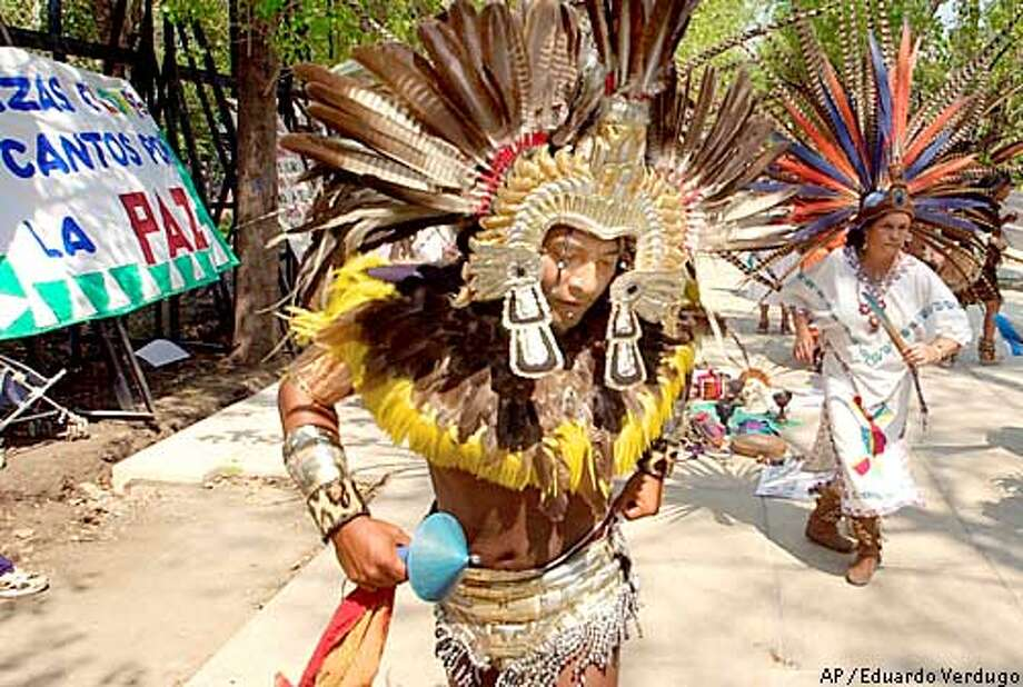 Dancers dressed as Azteca Indians perform outside of the U.S. embassy in Mexico City Feb. 25, 2003, against a possible U.S.-led war with Iraq. (AP Photo/Eduardo Verdugo) Photo: EDUARDO VERDUGO