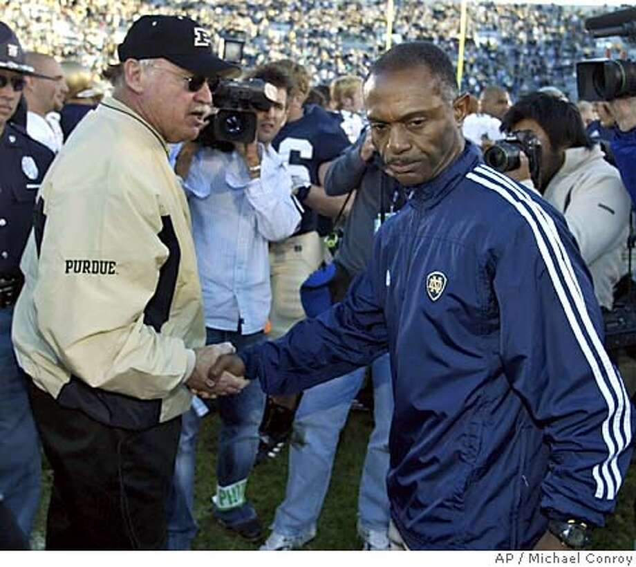 ** FILE ** Notre Dame coach Tyrone Willingham, right, congratulates Purdue coach Joe Tiller after Purdue defeated Notre Dame 41-16 in South Bend., Ind., in this Oct. 2, 2004 photo. The victory was the first for Purdue at Notre Dame since 1974. Notre Dame fired coach Willingham after three seasons, the school announced Tuesday Nov. 30, 2004. Willingham had a record of 21-15, including 6-5 this season. (AP Photo/Michael Conroy, FILE) Sports#Sports#Chronicle#12/1/2004#ALL#5star##0422492573 Photo: MICHAEL CONROY