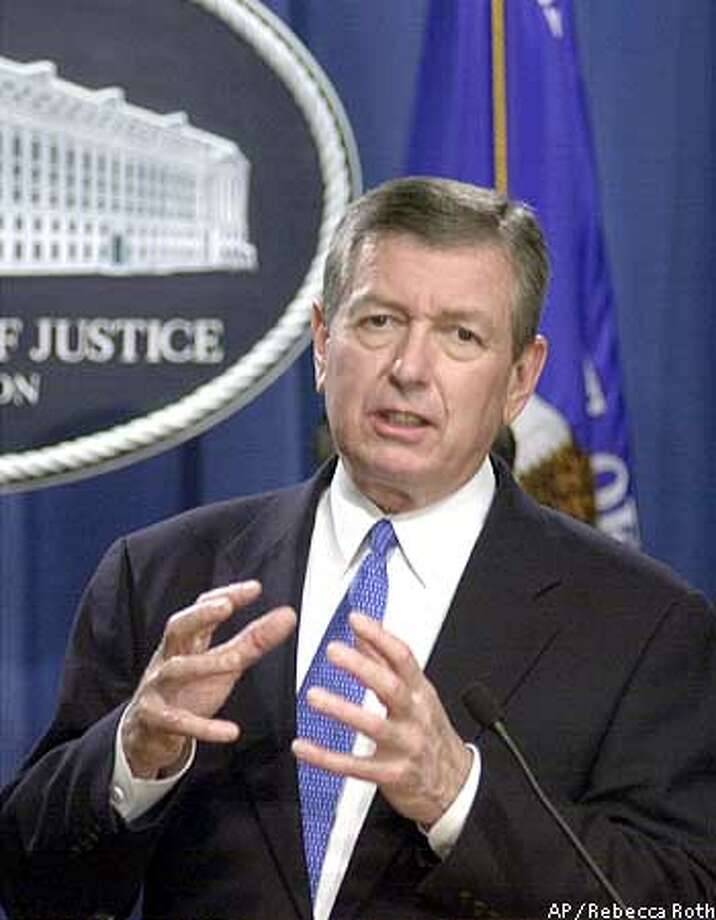 "Attorney General John Ashcroft gestures during a news conference at the Justice Department in Washington Monday, Feb. 24, 2003 to announce that three dozen people were charged Monday in federal indictments with trafficking in illegal from coast to coast, using both traditional stores and the Internet. Twenty-seven people were charged in 17 indictments returned by a grand jury western Pennsylvania as part of ""Operation Pipe Dreams,"" an investigation that stretched from Pittsburgh to Phoenix to southern California. (AP Photo/Rebecca Roth) Photo: REBECCA ROTH"