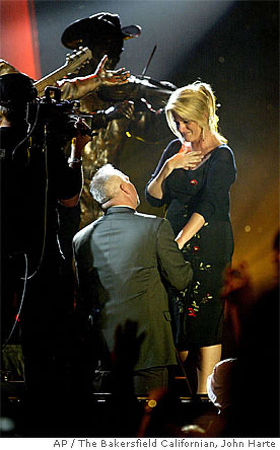 "Garth Brooks, left, proposes to Trisha Yearwood during the ""Legends in Bronze"" event at Buck Owens' Crystal Palace in Bakersfield, Calif., Wednesday, May 25, 2005. The Bakersfield Californian photo by John Harte via Associated Press"