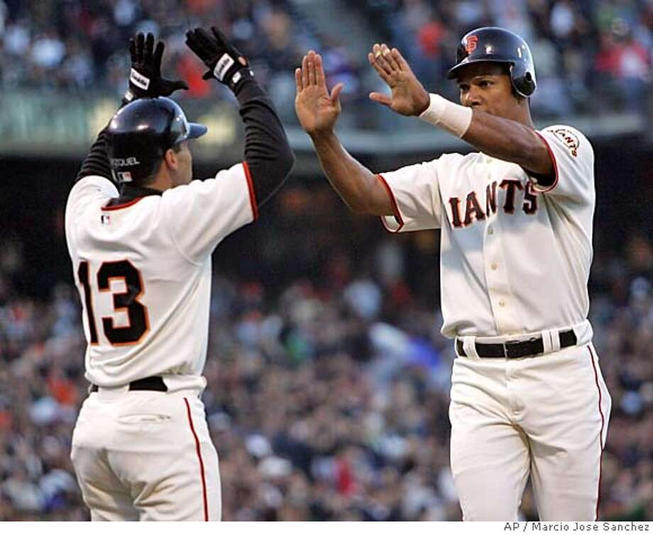 San Francisco Giants Moises Alou, right, is greeted at the plate by teaamate Omar Vizquel (13) after a three-run homerun off the Los Angeles Dodgers' Wilson Alvarez in the first inning on Wednesday, May 25, 2005 in San Francisco. (AP Photo/Marcio Jose Sanchez) Photo: MARCIO JOSE SANCHEZ