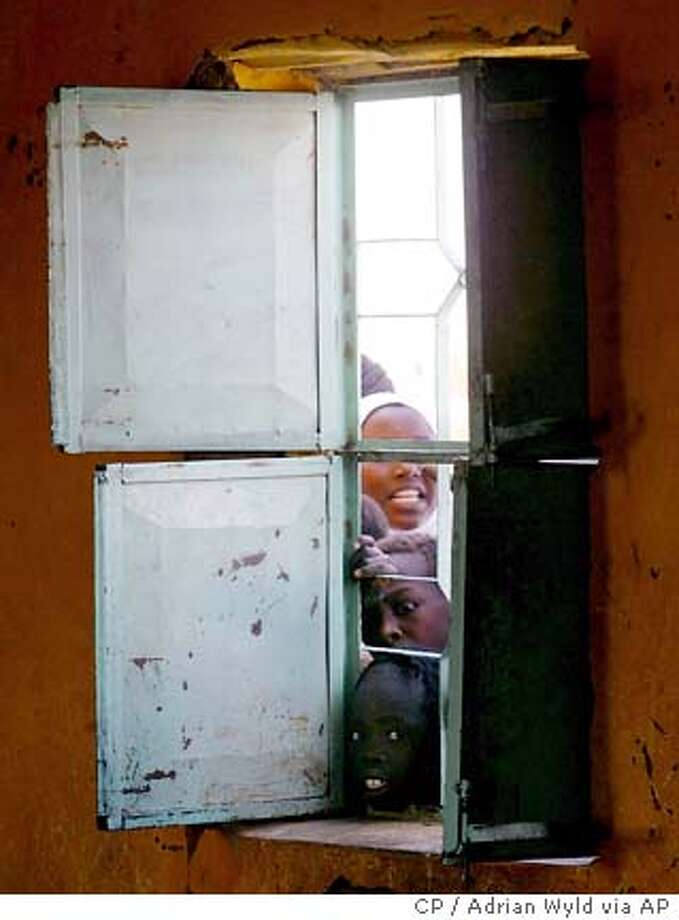 Children look in the window of a classroom as Canadian Prime Minister Paul Martin speaks to students during a visit to a camp for displaced persons in Khartoum, Sudan Thursday, Nov. 25, 2004. (AP Photo/CP, Adrian Wyld) Photo: ADRIAN WYLD
