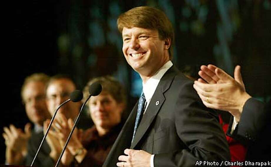 Democratic presidential hopeful, U.S. Sen. John Edwards of North Carolina, center, is applauded by committee leaders while making a speech to the Democratic National Committee in Washington Saturday, Feb. 22, 2003. The committee's three-day gathering, which ends Saturday, gave a crowded field of presidential hopefuls a chance to court the party's most active fund-raisers, political organizers and primary campaign voters. (AP Photo / Charles Dharapak) Photo: CHARLES DHARAPAK