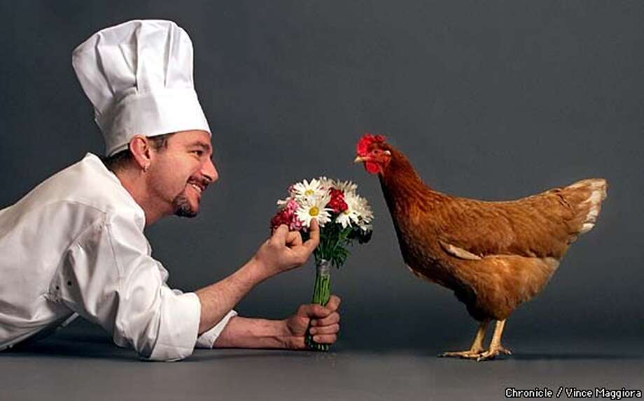 Chef Johnny Alamilla of Che restaurant holding out bouquet of flowers to a LIVE chicken... trying to re-romance the bird. Rekindling Your Romance With Chicken.  by Vince Maggiora Photo: VINCE MAGGIORA