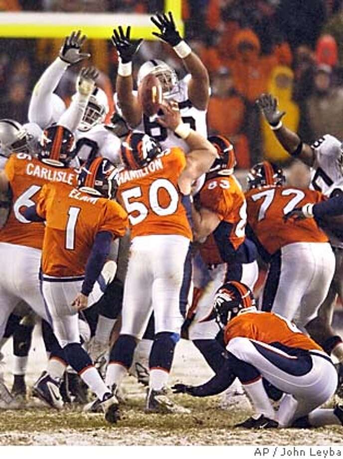 Oakland Raiders defensive tackle Langston Walker, center rear, blocks a field goal attempt by Denver Broncos' Jason Elam (1) late in the fourth quarter, Sunday, Nov. 28, 2004, in Denver. Broncos holder Micah Knorr, front right, holds for Elam. The Raiders won 25-24. (AP Photo/The Denver Post, John Leyba) DENVER OUT Sports#Sports#Chronicle#11/30/2004#ALL#5star##0422490518 Photo: JOHN LEYBA