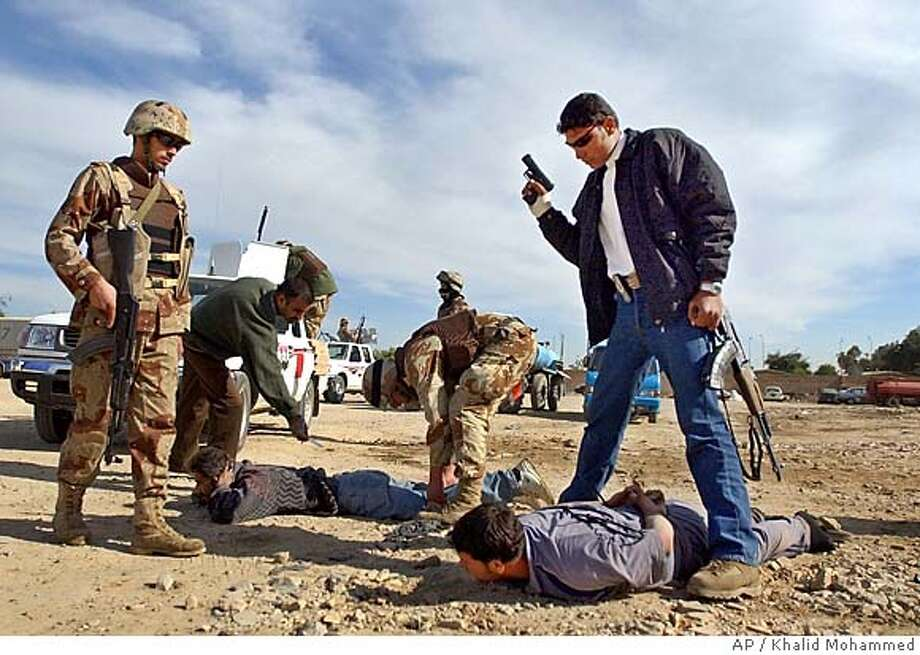 ** RETRANSMISSION FOR IMPROVED TONING ** Iraqi National Guard members arrests petrol black marketeers in Baghdad Monday Nov. 29, 2004. (AP Photo/Khalid Mohammed) Nation#MainNews#Chronicle#11/30/2004#ALL#5star##0422490763 Photo: KHALID MOHAMMED