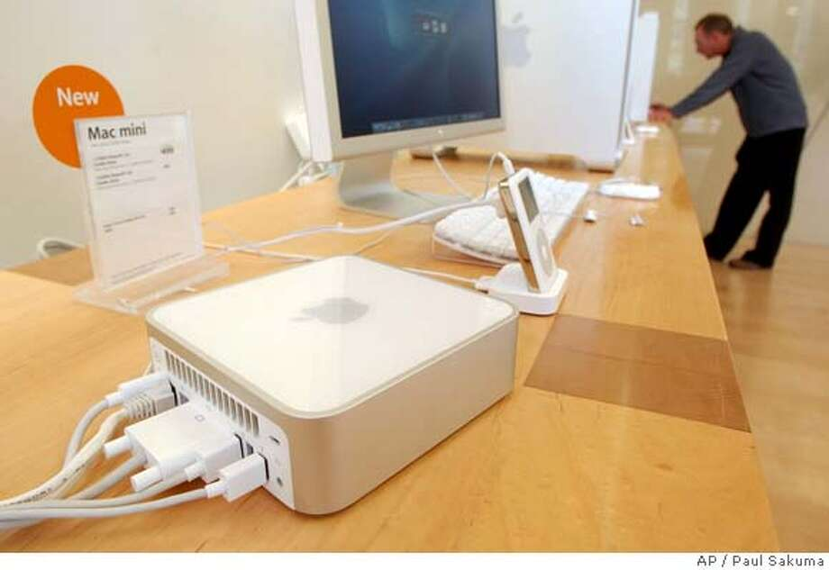 The Apple Computers Inc. new Mac Mini is shown at an Apple store in Palo Alto, Calif., Tuesday, Jan. 25, 2005. As it works to expand its share of the PC market, Mac is shippping a computer tha starts at $499. (AP Photo/Paul Sakuma) Ran on: 01-31-2005  Employee Phil Cohen holds up the new Mac Mini at the Apple Store in Palo Alto. HOLD FOR FUTURE USE Photo: PAUL SAKUMA