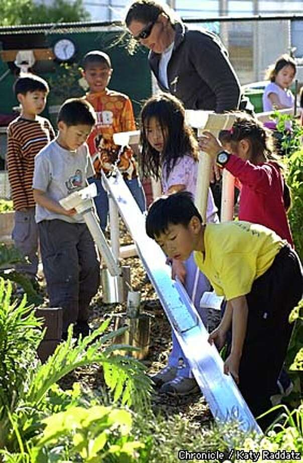 Second-graders at Alice Fong Yu Elementary School work on the garden's irrigation system as Arden Bucklin-Sporer, rear, supervises. Chronicle photo by Katy Raddatz