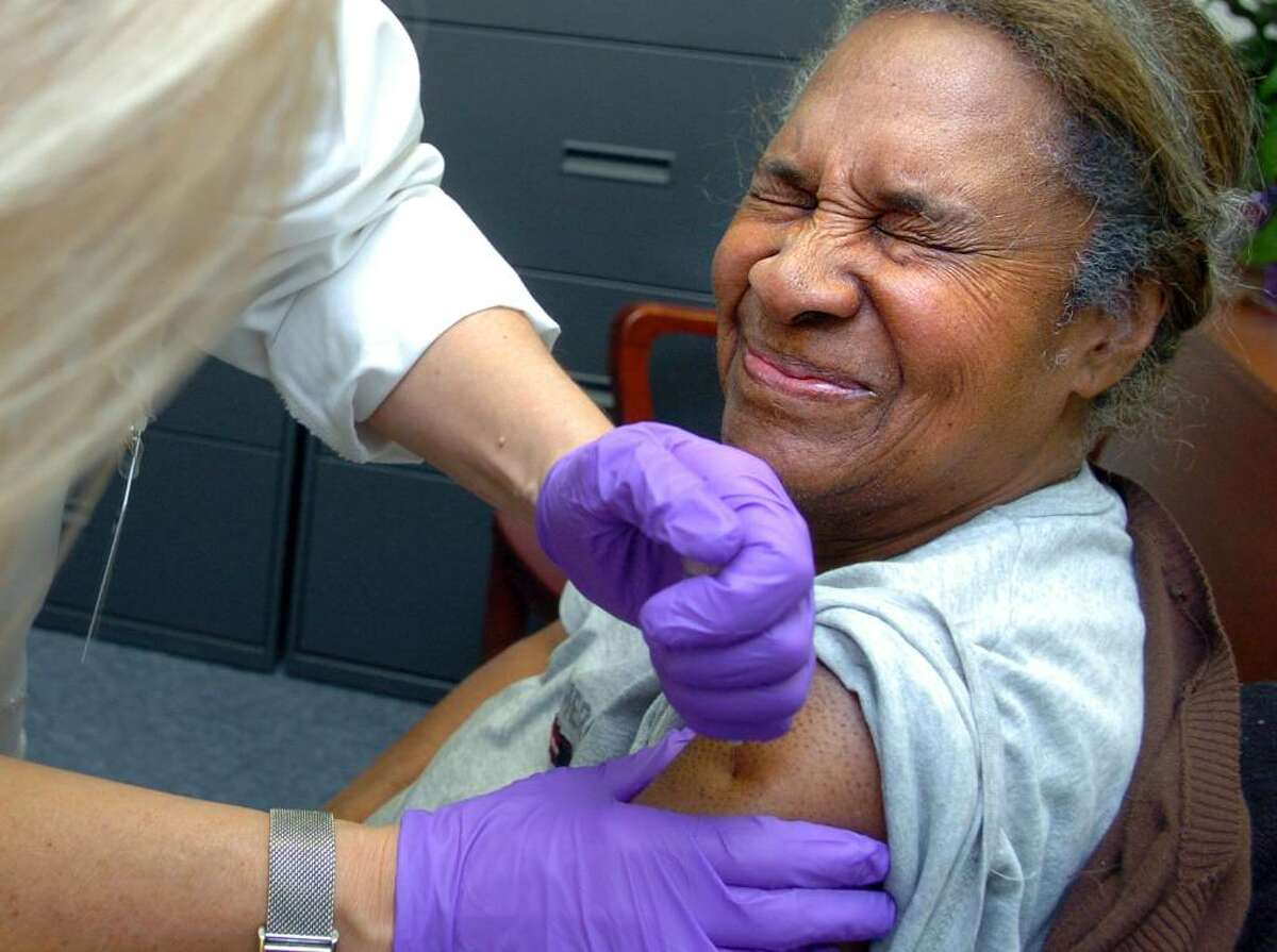Joan Brockenberry, of Milford, braces herself as she gets the H1N1 vaccine Thursday night at the Milford Health Department.