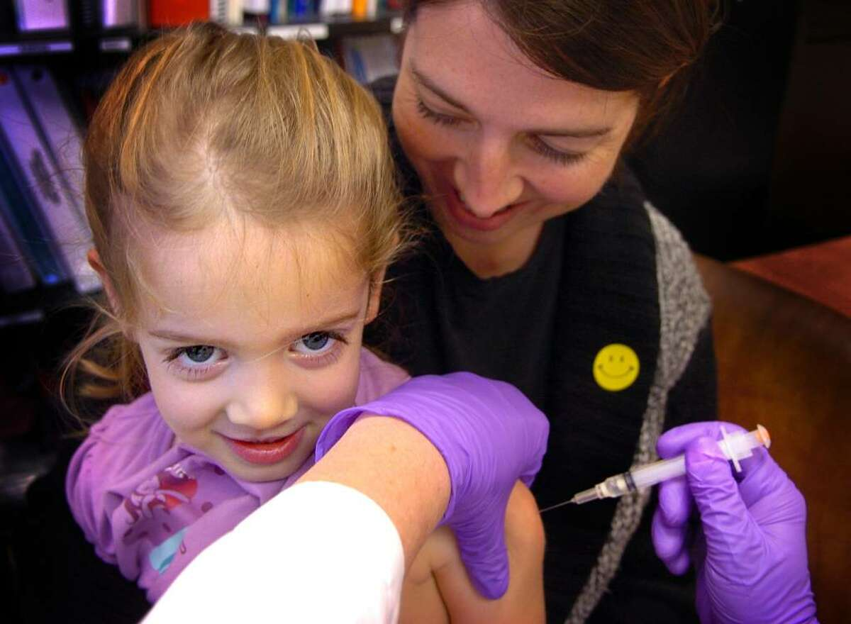 Three-year-old Isabelle Maselli, of Milford, on mom Abigail's lap, doesn't even flinch as she gets the H1N1 vaccine Thursday night at the Milford Health Department.