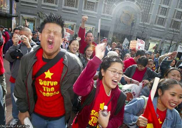 Filipinos for Global Justice, NotWar, got into the swing of things as they made their way down Market Street...l-r Paolo Sambrano, Lillian Prijoles and Ivy Climacosa led the way. By Kat WAde/Chronicle Photo: KAT WADE