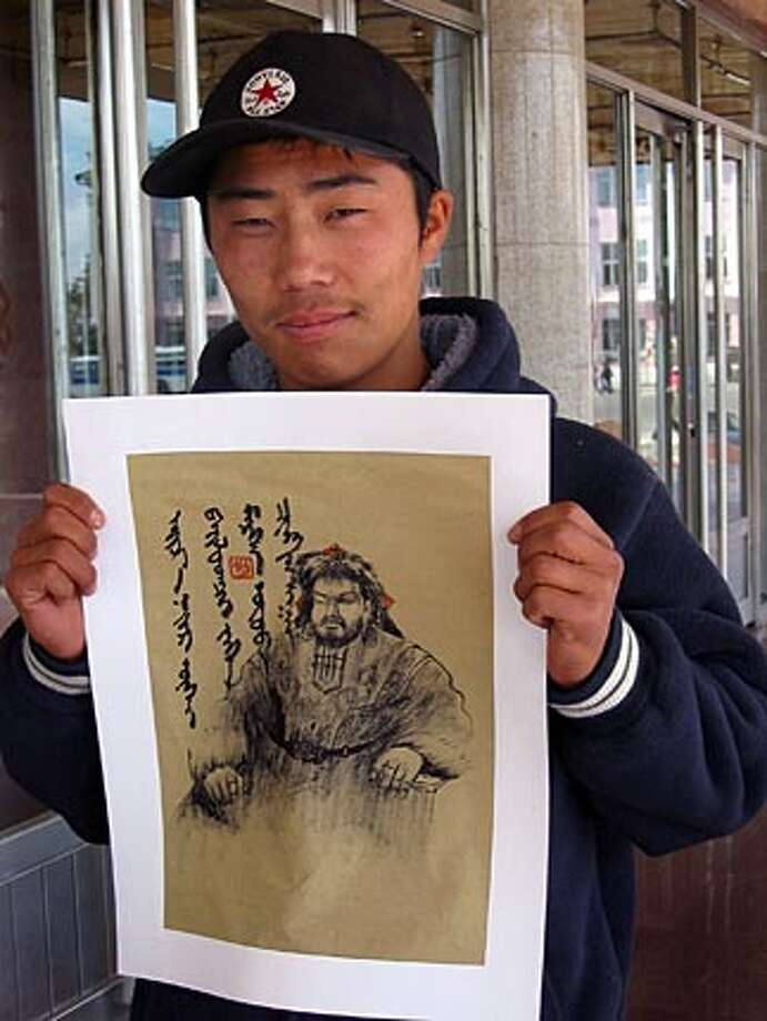 Uchral, 20,�a painter in Mongolia, with his portrait of Genghis Khan.