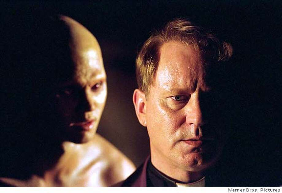 "In this photo provided by Warner Bros. Pictures, Cheche ( Billy Crawford) stand behind Father Lankester Merrin (Stellan Skarsgard) in ""Dominion: A Prequel to the Exorcist."" (Warner Bros. Pictures)"