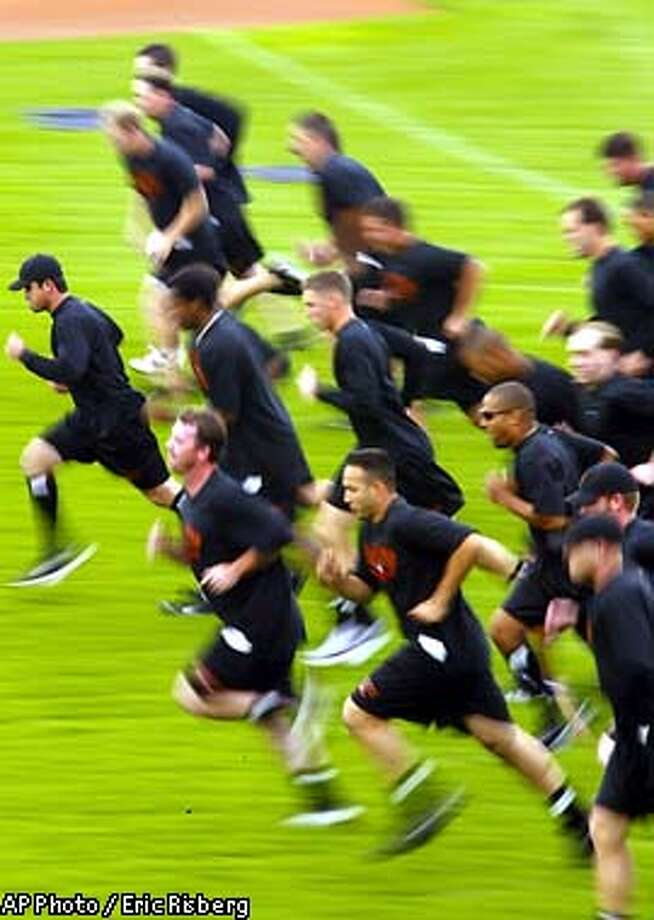 San Francisco Giants' pitchers and catchers run across the field in a drill at Scottsdale Stadium during the first day of their spring training workouts in Scottsdale, Ariz., Saturday Feb. 15, 2003.(AP Photo/Eric Risberg) Photo: ERIC RISBERG