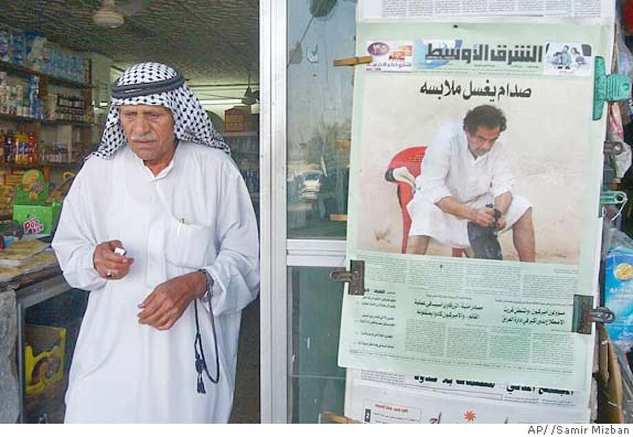 ** EDITORS NOTE : THIS IMAGE MUST BE USED IN ITS ENTIRETY ** A customer walks out from a general store past a copy of the Saturday edition of Iraq's Asharq al-Awsat newspaper, showing a picture of Saddam Hussein seated in a white robe which was originally used on Friday's front page of Britain's mass circulation tabloid newspaper the Sun, in central Baghdad, Iraq Saturday, May 21, 2005. (AP Photo/Samir Mizban) Photo: SAMIR MIZBAN