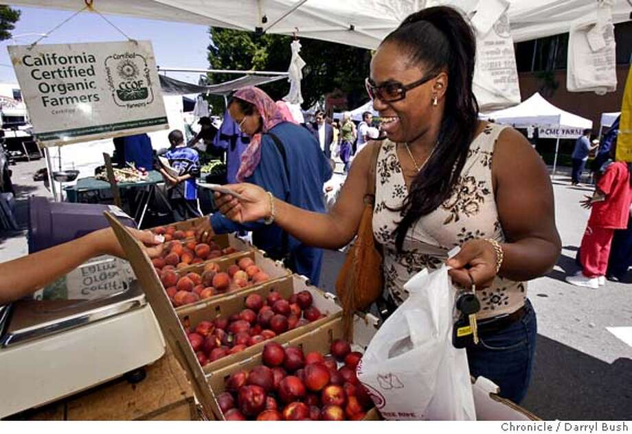 bayview_002_db.jpg  Sabryna Moore of Antioch who grew up in Hunters Point and still visits and volunteers locally buys some organic nectarines at one of the farmer's stands at the newly created Bayview Hunters Point Farmers' Market on 3rd Street.  Event on 5/21/05 in San Francisco.  Darryl Bush / The Chronicle MANDATORY CREDIT FOR PHOTOG AND SF CHRONICLE/ -MAGS OUT Photo: Darryl Bush