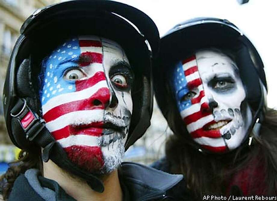 Protestors painted half with the American flag and half with a death mask take part in a peace rally in Paris, France Saturday, Feb. 15, 2003. Thousands of demonstrators gathered to protest a possible U.S.- led war on Iraq. (AP Photo/Laurent Rebours) Photo: LAURENT REBOURS