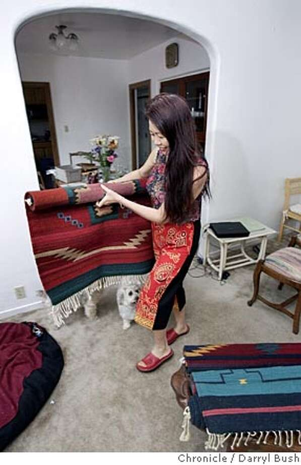 """rentvsbuy22_002_db.jpg  Margaret Chau unpacks a decorative rug at her new home she is renting. Her two small terriers are, """"Riley (with the darker face)"""" and """"Katy.""""  Event on 5/19/05 in Millbrae.  Darryl Bush / The Chronicle MANDATORY CREDIT FOR PHOTOG AND SF CHRONICLE/ -MAGS OUT Photo: Darryl Bush"""