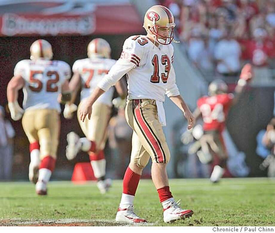 Tim Rattay walks slowly off the field after throwing a 55-yard interception returned for a touchdown by Tampa Bay's Torrie Cox seen celebrating (background, right) in the fourth quarter. San Francisco 49ers vs. Tampa Bay Buccaneers at Raymond James Stadium on 11/21/04 in Tampa, FL. PAUL CHINN/The Chronicle Photo: PAUL CHINN