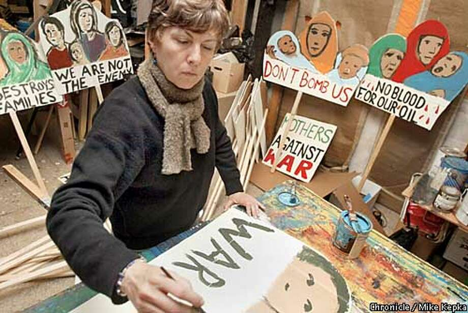 At a labor hall in the Mission, Cathrine Margerin, volunteer with a political action group called Art and Revolution, works on her message for Sunday's peace rally. BY MIKE KEPKA/THE CHRONICLE Photo: MIKE KEPKA
