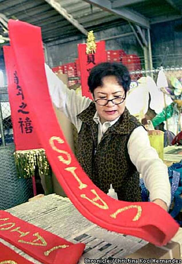 CHRISTINA KOCI HERNANDEZ/CHRONICLE  Teresa Hei works on banners for the Chinese Ameran International School float. Last minute touches to Chinatown Parade floats at pier27-29, in SF. Photo: CHRISTINA KOCI HERNANDEZ
