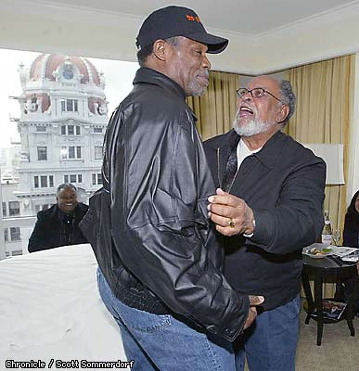 The Rev. Cecil Williams greeted Danny Glover in the morning as they assembled to start the march down Market St to protest a possible American invasion of Iraq. By Scott Sommerdorf/Chronicle