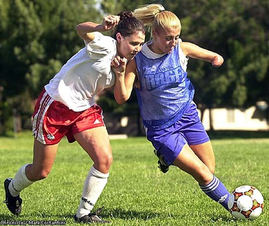 Judy Coffman, right, fends off Taylor Wood, of the University of Virginia, at a Pleasanton Rage practice last summer. Coffman heads to the University of Michigan this summer on a soccer scholarship. Chronicle photo, 2002, by Mark Costantini