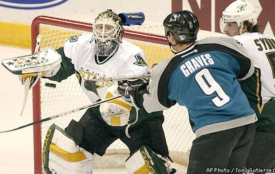 Dallas Stars goalie Ron Tugnutt, left, deflects a puck as San Jose Sharks' Adam Graves, (9) attemps to slap it in during the first period, Sunday Feb. 16, 2003, in Dallas. Stars teammate Darryl Sytdor, right, helps defend on the play. (AP Photo / Tony Gutierrez) Photo: TONY GUTIERREZ