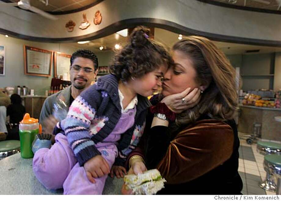 AIRPORTCROWDS_056_kk.jpg  Jinan Jiha, 2, of Pacifica kisses her mother Nadine Jiha as they wait for their flight at SFO Wednesday. Nadine's brother Judeh Bahnan is in the background. The Jinan family arrived very early for their flight, expecting crowds. Chronicle photo by Kim Komenich at SFO Nation#MainNews#Chronicle#11/25/2004#ALL#5star##0422484828