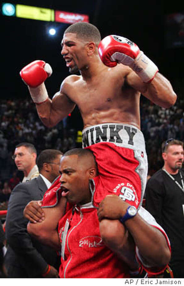 Winky Wright, of St. Petersburg, Fla., celebrates his win over Felix Trinidad, of Puerto Rico, in their middleweight fight on Saturday, May 14, 2005,at the MGM Grand Garden Arena. Wright won by unanimous decision after 12 rounds. The man Wright is riding on is unidentified. (AP Photo/Eric Jamison) Photo: ERIC JAMISON