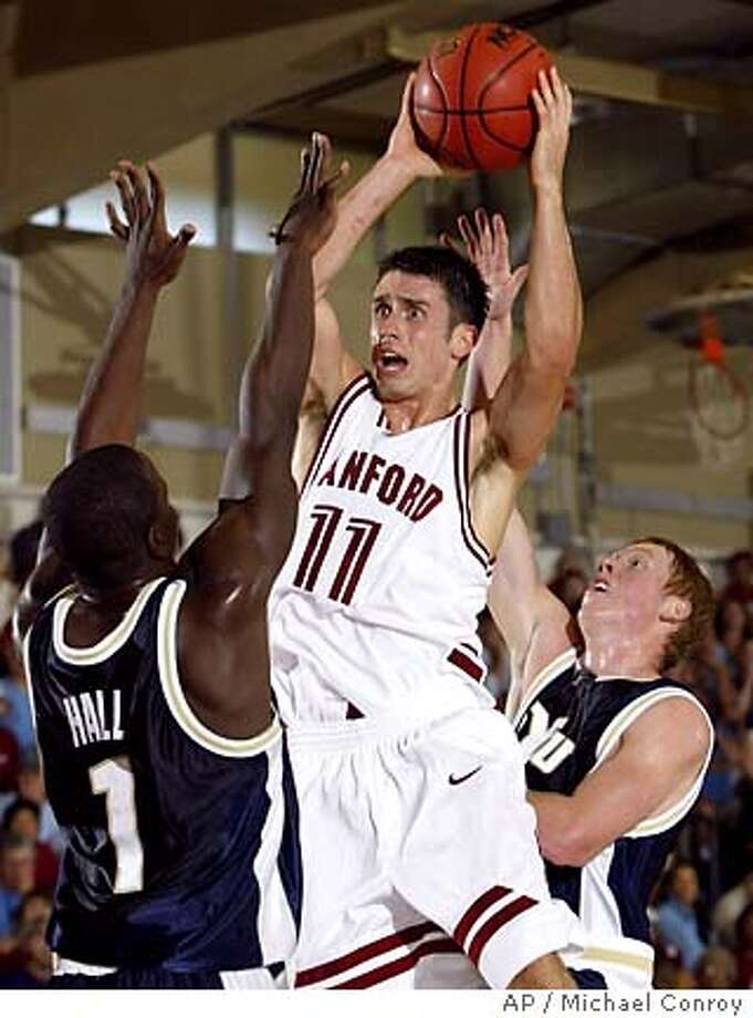 Stanford's Chris Hernandez, center, pulls down a long rebound between BYU's Mike Hall, left, and Mike Rose in the first half in the consolation bracket of the Maui Invitational in Lahaina, Hawaii, Tuesday, Nov. 23, 2004. (AP Photo/Michael Conroy) Photo: MICHAEL CONROY