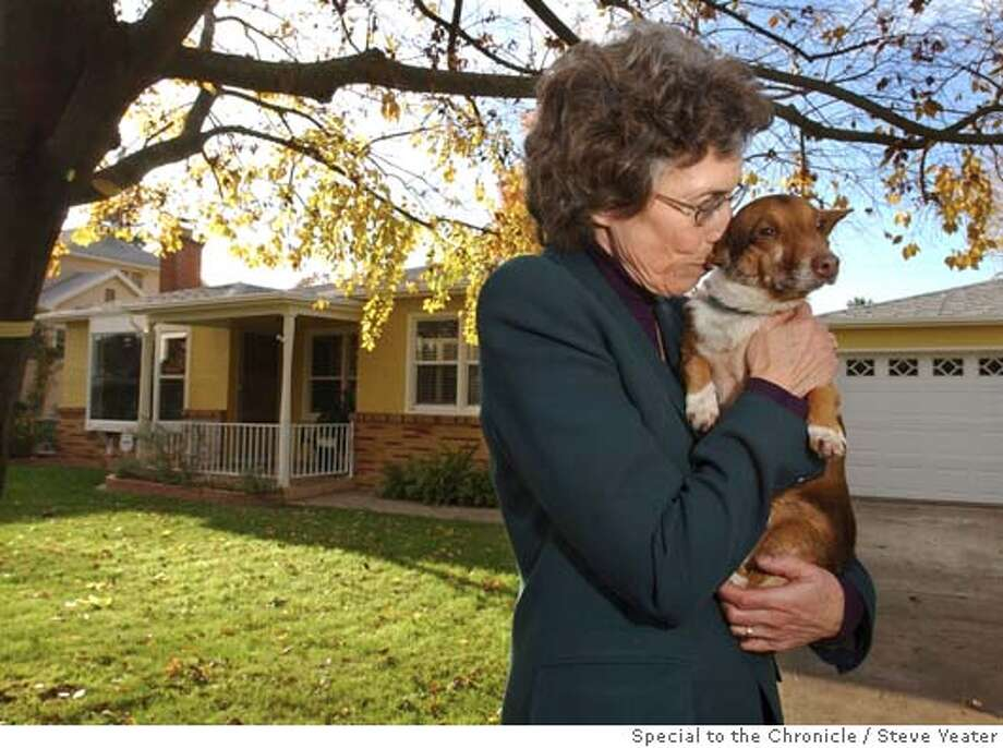 Charlotte Cook gives Travis the dog a kiss while standing in front of the home that belonged to her neighbor Leo Travis in Sacramento, Calif., on Friday, Nov. 19, 2004. Cook adopted the dog that belonged to Mr.Travis after his death. (Photo/Steve Yeater) Business#Business#Chronicle#11/20/2004##5star##0422475956 Photo: Steve Yeater For The Chronicle