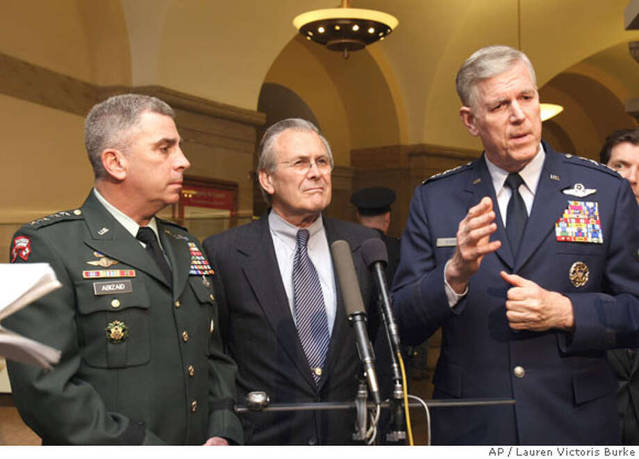 U.S. Joint Chiefs Chairman Gen. Richard Myers, right, accompanied by Defense Secretary Donald H. Rumsfeld, center, and Gen. John Abizaid, commander of the U.S. Central Command, gestures while talking to reporters on Capitol Hill in Washington, D.C., Wednesday, May 18, 2005 after a closed-door meeting with members of Congress to discuss the situation in Iraq. (AP Photo/Lauren Victoris Burke) Photo: LAUREN VICTORIA BURKE
