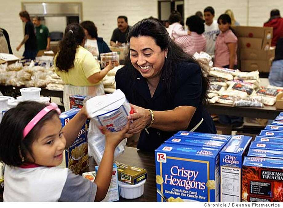 pnfood_001_df.JPG  Blanca Castillo volunteers at the Food Bank in Redwood City. She is giving sugar to Esmerelda Ramirez, 6. Blanca is a single mother and a part-time substitute teacher in Redwood City , doesn't make enough money to put enough food on the table for she and her son so she turns to Second Harvest Food bank of San Mateo and Santa Clara Counties for help. Deanne Fitzmaurice / The Chronicle Photo: Deanne Fitzmaurice