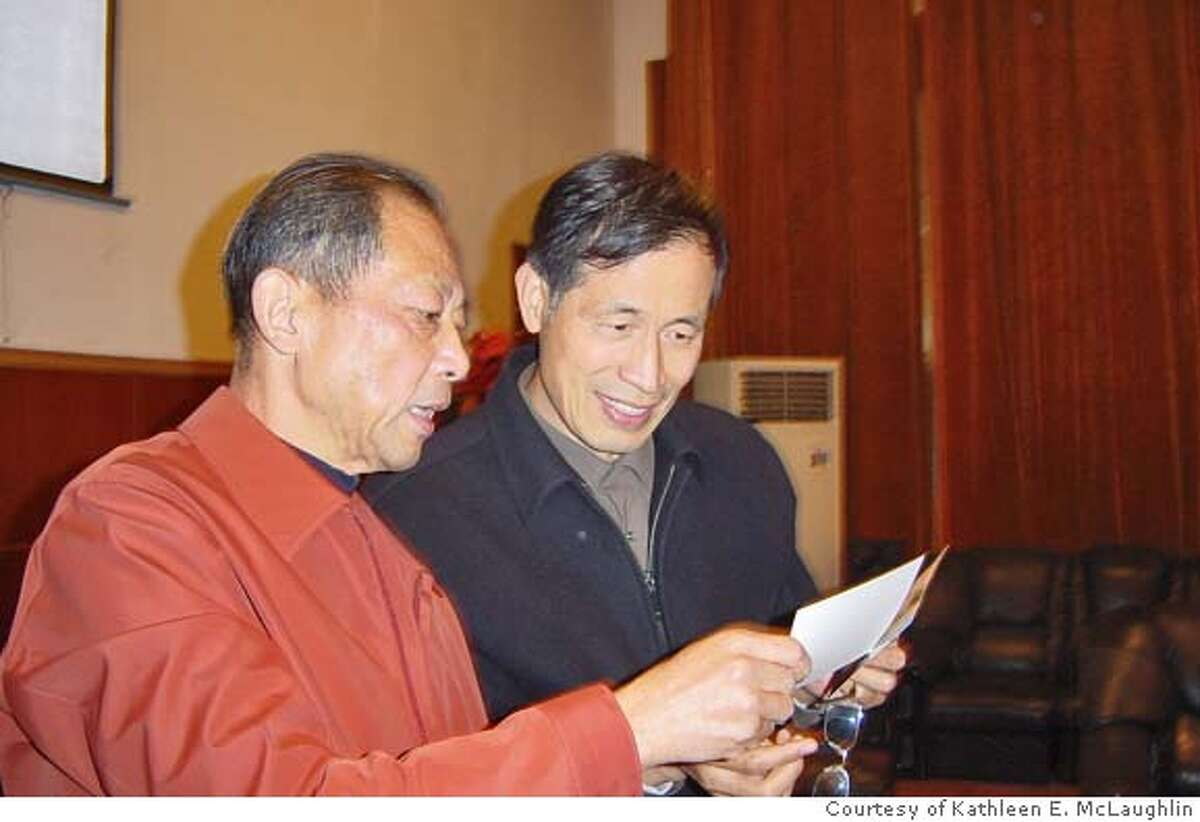 Professor Sun Zhaiwei, here showing Jiangsu Province official Jiang Jiangming photos of he and Iris Chang, helped Chang with research in Nanjing and recalls being impressed with her intelligence and passion for her work. Sun says Chang added immensely to the overall body of historical work about the Nanjing Massacre.