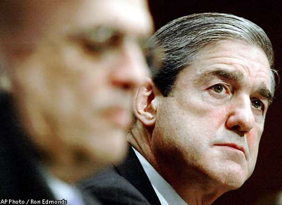 FBI Director Robert Mueller, right, listens to CIA Director George Tenet, left, testify, Tuesday, Feb. 11, 2003, before the Senate Intelligence Committee in Washington. Tenet and Mueller say al-Qaida still poses the greatest terror threat to America, but that their agencies are far better prepared to detect and head off attacks than they were before Sept. 11, 2001. (AP Photo/Ron Edmonds) Photo: RON EDMONDS
