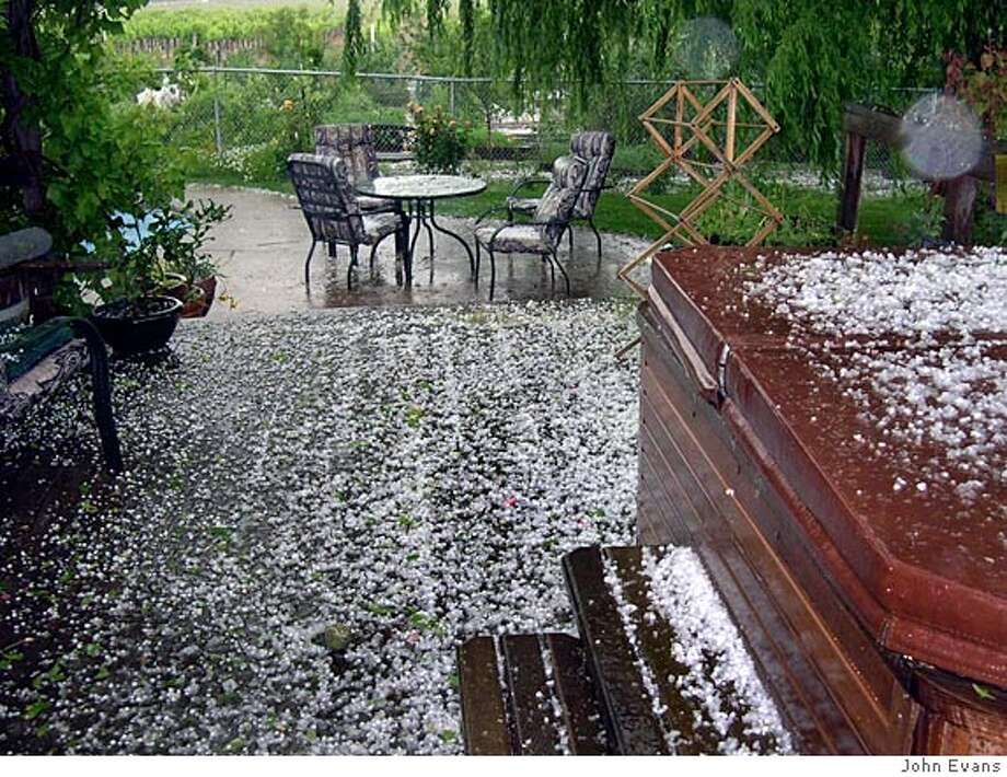 Hailstones covered the deck and wreaked havoc with the garden on Monday. Photo by John Evans Photo: John Evans
