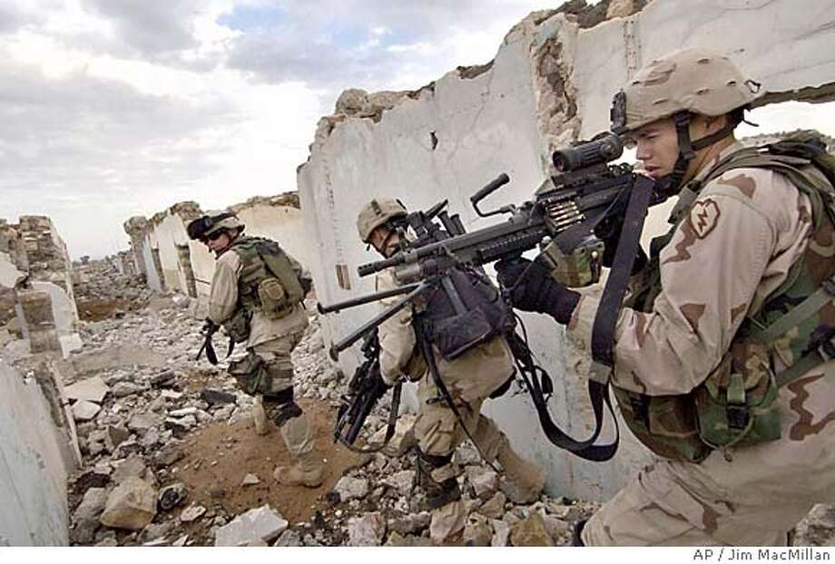 U.S. Army soldiers search for insurgents suspected of planting a roadside bomb in Mosul, Iraq Sunday, Nov. 21, 2004. U.S. and Iraqi forces in Mosul have been working put down an uprising launched by guerrillas who seized police stations and other sites. The uprising was part of a wave of violence across the country coinciding with the U.S. offensive against the insurgent stronghold of Fallujah. (AP Photo/Jim MacMillan) #MainNews#Chronicle#11/22/2004####0422478691 Photo: JIM MACMILLAN