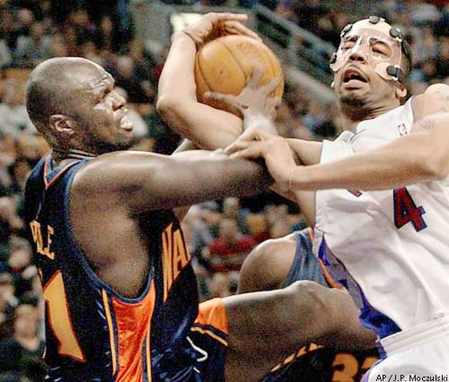 Golden State Warriors centerAdonal Foyle, left, battles Toronto Raptors' center Jelani McCoy, who is wearing a faceguard to protect a broken nose, for posession during first half NBA play in Toronto on Friday, Feb. 14, 2003. (AP Photo/J.P. Moczulski) Photo: J.P. MOCZULSKI