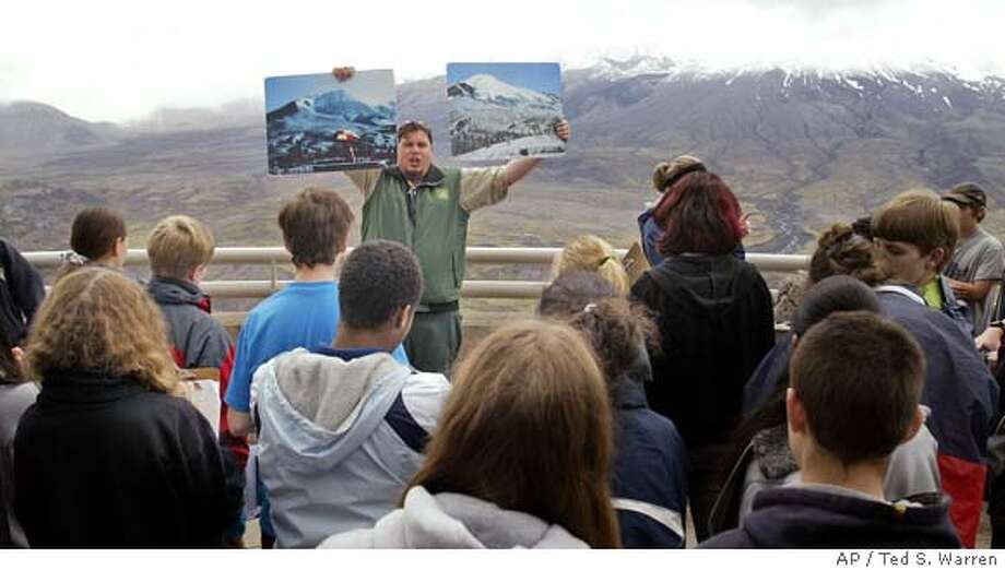 Jason Harrison, a seasonal park ranger with the U.S. Forest Service, talks to students from Mt. Tabor Middle School in Portland, Ore. at the Johnston Ridge Observatory at Mount St. Helens as he holds up photographs Tuesday, May 17, 2005, of the volcano that were taken before a massive explosive eruption altered its shape and killed 57 people on May 18, 1980. Wednesday will mark the 25th anniversary of the blast. The actual volcano is mostly obscured by clouds behind Harrison. (AP Photo/Ted S. Warren) Ran on: 05-18-2005  Jason Harrison, a U.S. Forest Service park ranger, left, holds up photographs as he talks to students about Mount St. Helens, right. Photo: TED S. WARREN