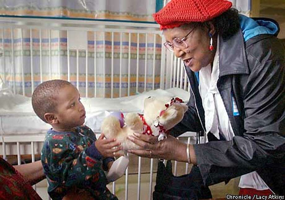 Daniel Locks,l a patient at the Childrens Hospital in Oakland, receives a teddy bear for valentines from Mary Hillard of the Center for Elders Independence, Friday Feb.14,03, in Oakland. The group of elderly women decorated the bears and delievered them to the Children to help celebrate Valentines Day.  SAN FRANCISCO CHRONICLE/LACY ATKINS Photo: LACY ATKINS
