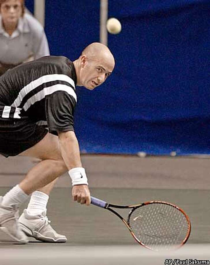 Top-seeded Andre Agassi returns a shot to Vladimir Voltchkov in the in San Jose, Calif., Friday, Feb. 14, 2003. (AP Photo/Paul Sakuma) Photo: PAUL SAKUMA
