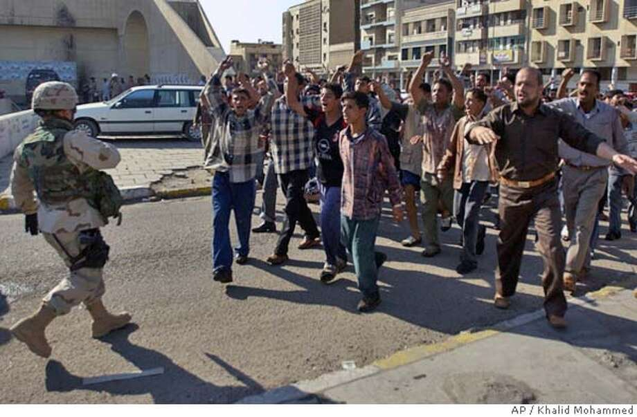 A U.S. soldier walks backwards as a group of Iraqis advance chanting anti-government and anti-US slogans after a car bomb exploded killing at least one person in downtown Baghdad Saturday Nov. 20, 2004. (AP Photo/Khalid Mohammed) Photo: KHALID MOHAMMED