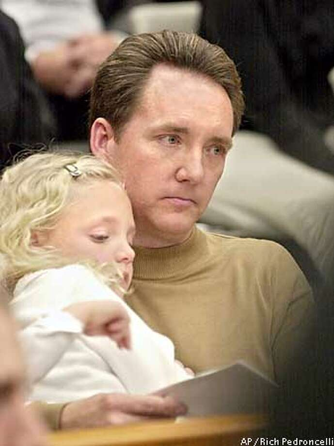 Holding his daughter, Falon, 7, Jon Opsahl, listens to the sentencing of the four former Symbionese Liberation Army members responsible for his mother's murder during a hearing in Sacramento Superior Court, Friday, Feb. 14, 2003, in Sacramento, Calif. Myrna Opsahl, the mother of four, was depositing her church's collection funds when she was shot during the SLA's robbery of the Crocker National Bank in suburban Carmichael, Calif. in 1975. Four former SLA members were sentenced under a plea agreement to prison terms ranging from six to eight years for the crime. (AP Photo/Rich Pedroncelli) Photo: RICH PEDRONCELLI