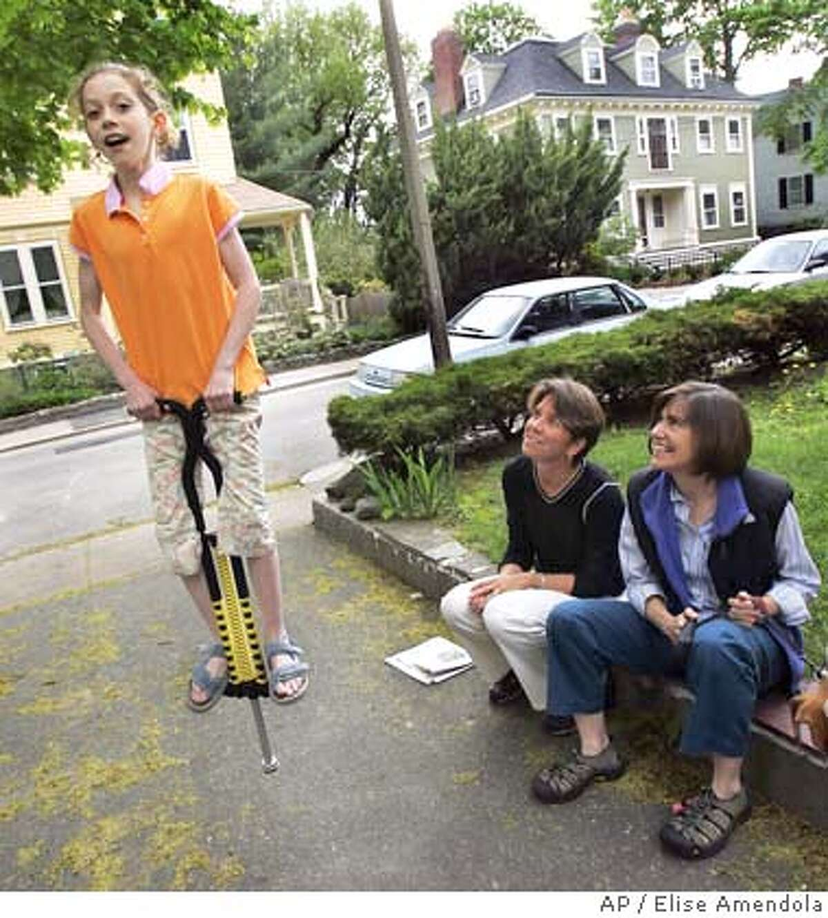 Hillary, left, and Julie Goodridge watch their nine-year-old daughter, Annie, jump on a pogo stick in their driveway in Boston's Jamaica Plain section Saturday, May 14, 2005. Julie and Hillary Goodridge, the couple whose names were immortalized as the lead plaintiffs in the lawsuit against the state, carry copies of their wedding licenses with them everywhere they go, in case they have to prove they're married in an emergency. May 17 is the one-year anniversary of gay marriage in Massachusetts. (AP Photo/Elise Amendola)