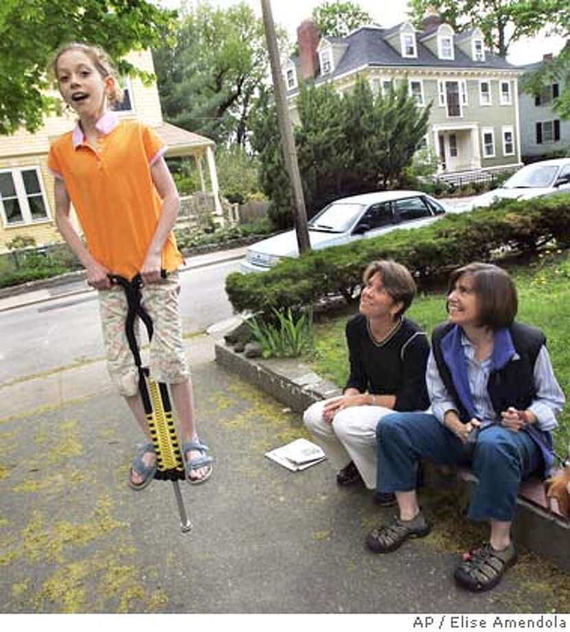 Hillary, left, and Julie Goodridge watch their nine-year-old daughter, Annie, jump on a pogo stick in their driveway in Boston's Jamaica Plain section Saturday, May 14, 2005. Julie and Hillary Goodridge, the couple whose names were immortalized as the lead plaintiffs in the lawsuit against the state, carry copies of their wedding licenses with them everywhere they go, in case they have to prove they're married in an emergency. May 17 is the one-year anniversary of gay marriage in Massachusetts. (AP Photo/Elise Amendola) Photo: ELISE AMENDOLA