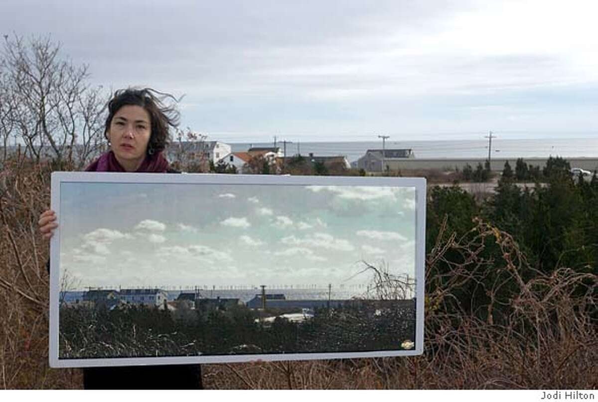 CENTERVILLE, MASS.--Audra Parker, Assistant director at the Alliance to Protect Nantucket Sound, holds a photographic simulation which shows how the proposed wind farm would look to residents who live above Craigsville Beach on Cape Cod. CREDIT: JODI HILTON